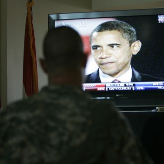 A U.S. soldier and an Embassy official watch on TV, the U.S. President-elect Barack Obama, during a post-election event inside U.S Embassy, in Baghdad on November 05, 2008. Crocker said that America unleashed a new stage in history when American people had elected an African-American President Barack Obama. AFP PHOTO/Petros Giannakouris-POOL (Photo credit should read PETROS GIANNAKOURIS/AFP/Getty Images)