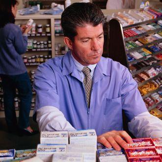 Pharmacist at Drug Shelves.