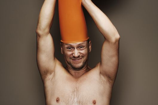 Man pulling at orange inflated balloon on head, portrait, close-up