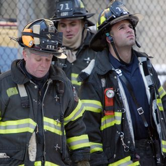 New York City fire crews look up at the building where two firemen were killed and four critically injured in an early morning fire in the Bronx borough of New York Sunday, Jan. 23, 2005.