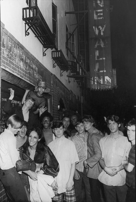 An unidentifed group of young poeple celebrate outside the boarded-up Stonewall Inn (53 Christopher Street) after riots over the weekend of June 27, 1969. The bar and surrounding area were the site of a series of demonstrations and riots that led to the formation of the modern gay rights movement in the United States. (Photo by Fred W. McDarrah/Getty Images)
