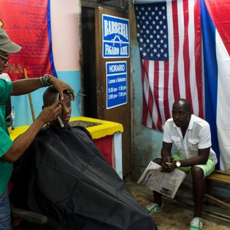 Havana Cuba. The Cuban and the American flag fly together in a barber shop in Havana.Havana life. People go to work, walk the dog, children go to school, shops are opening, people wait on line, people practice Tai Chi in the park.
