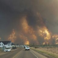 This photo take through a car windshield shows smoke rising from a wildfire rages outside of Fort McMurray, Alberta, Tuesday, May 3, 2016. The entire population of the Canadian oil sands city of Fort McMurray, has been ordered to evacuate as a wildfire whipped by winds engulfed homes and sent ash raining down on residents. (Mary Anne Sexsmith-Segato/The Canadian Press via AP) MANDATORY CREDIT