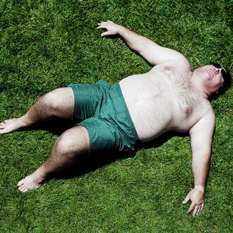 Large man lying on grass, wearing shorts, elevated view