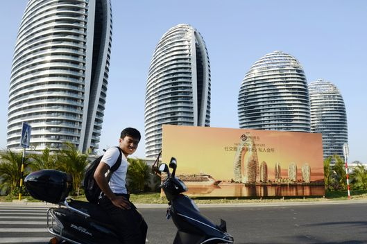 This picture taken on January 19, 2013 shows a Chinese man sitting on a motorbike in front of luxury apartment blocks at the seaside city of Sanya, in China's southern Hainan province.  It was billed as China's Dubai: a cluster of sail-shaped skyscrapers on a manmade island surrounded by tropical sea, the epitome of an unprecedented property boom that transformed skylines across the country.  But prices on Phoenix Island, off the palm-tree lined streets of the resort city of Sanya, have plummeted in recent months, exposing the hidden fragilities of China's growing but sometimes unbalanced economy.