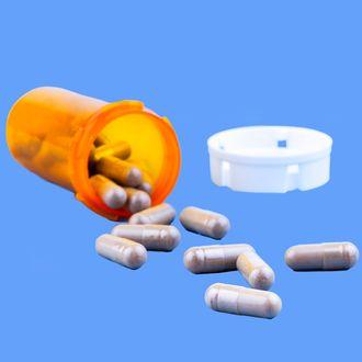 Pills and open bottle, studio shot.