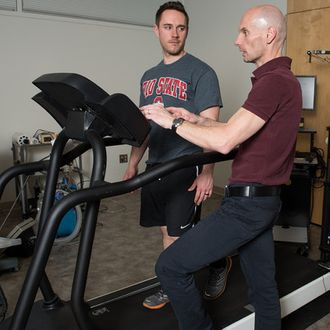 Steven Devor, front, discusses the new automated treadmill with doctoral student Rich LaFountain.