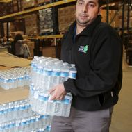 Food Bank of Eastern Michigan worker Filipovich helps to load bottled water in the agency's warehouse that will be distributed to the public, after elevated lead levels were found in the city's water in Flint