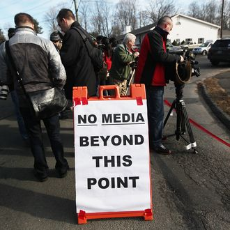 NEWTOWN, CT - DECEMBER 15: Media gather near a makeshift memorial outside a firehouse which was used as a staging area for families following the mass shooting at Sandy Hook Elementary School on December 15, 2012 in Newtown, Connecticut. Twenty six people were shot dead, including twenty children, after a gunman identified as Adam Lanza in news reports opened fire in the school. Lanza also reportedly had committed suicide at the scene. (Photo by Mario Tama/Getty Images)