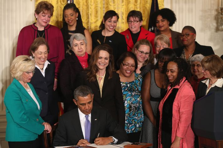 U.S. President Barack Obama is flanked by Lilly Ledbetter (L) and other women while signing an executive order banning federal contractors from retaliating against employees during an event in the East Room of the White House on April 8, 2014 in Washington, DC. President Obama announced that his administration will strengthen enforcement of equal pay laws for women.