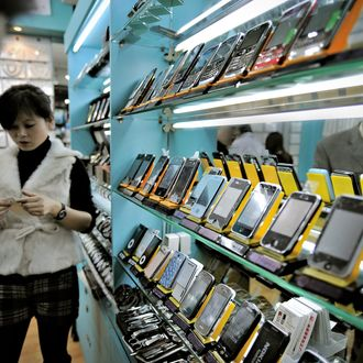 This picture taken on November 13, 2009 shows a man (L) looking at fake iPhones displayed in a shop at a market known for counterfeit US goods and housed in the metro station connected to the Science and Technology Museum in Shanghai. Barack Obama on November 16, 2009 became the third US president to make his mark at the Shanghai Science and Technology Museum when he staged a town hall-style meeting there with hundreds of Chinese students. AFP PHOTO / PHILIPPE LOPEZ (Photo credit should read PHILIPPE LOPEZ/AFP/Getty Images)