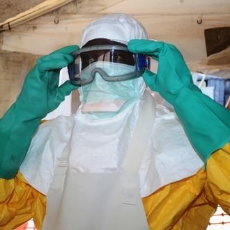 A picture taken on June 28, 2014 shows a member of Doctors Without Borders (MSF) putting on protective gear at the isolation ward of the Donka Hospital in Conakry, where people infected with the Ebola virus are being treated. The World Health Organization has warned that Ebola could spread beyond hard-hit Guinea, Liberia and Sierra Leone to neighbouring nations, but insisted that travel bans were not the answer. To date, there have been 635 cases of haemorrhagic fever in Guinea, Liberia and Sierra Leone, most confirmed as Ebola. A total of 399 people have died, 280 of them in Guinea. AFP PHOTO / CELLOU BINANI (Photo credit should read CELLOU BINANI/AFP/Getty Images)