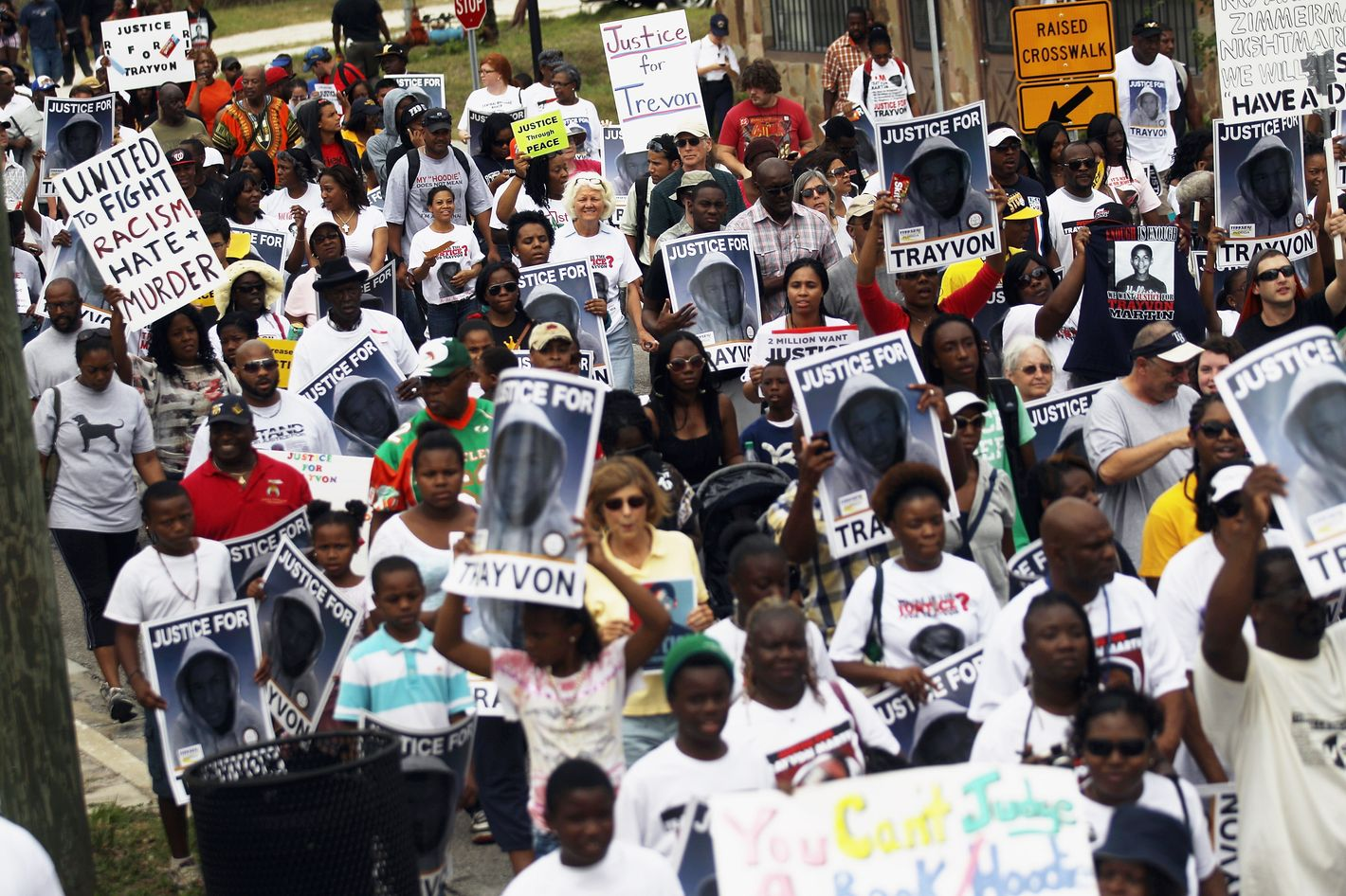 SANFORD, FL - MARCH 31: Trayvon Martin supporters march through the historically African American community of Goldsboro on their way to an NAACP rally in front of the Sanford Police Department on March 31, 2012 in Sanford, Florida. Martin was killed by George Michael Zimmerman while on neighborhood watch patrol in the gated community of The Retreat at Twin Lakes. Rev. Jesse Jackson, Rev. Al Sharpton and NAACP President Benjamin Jealous were amongst the supporters demanding Zimmerman's arrest. (Photo by Mario Tama/Getty Images)