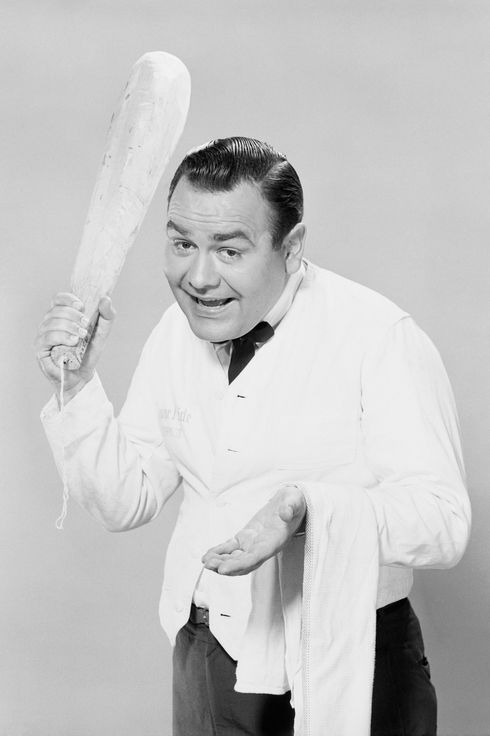 Jonathan Winters brandishes a loaf of bread, acting the part of a waiter at a large restaurant asking for a tip.