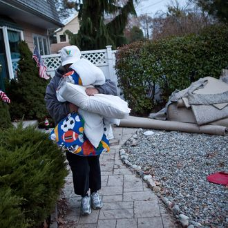 Trisha McAvoy carries bedding to her car while evacuating from her home due to an approaching storm on November 6, 2012 in Brick Township, New Jersey. As the New Jersey coastline continues to recover from Hurricane Sandy, numerous polling stations have had to be relocated and aggregated together, due to storm damage and power outages.