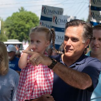 WOLFEBORO, NH - JULY 4: Republican presidential candidate, former Massachusetts Gov. Mitt Romney holds his granddaughter Soleil Romney, 3 as he walks in the Wolfeboro Independence Day parade on July 4, 2012 in Wolfeboro, New Hampshire. The Romney's took a break from their vacation to march in the parade. (Photo by Kayana Szymczak/Getty Images)