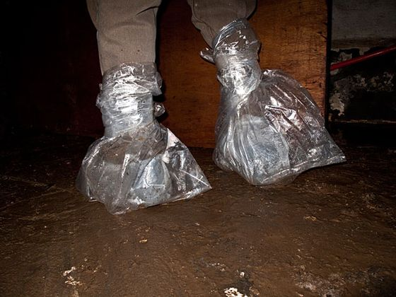 Worker's plastic bag-wrapped feet in the flooded basement of a Battery Park area pizzeria.