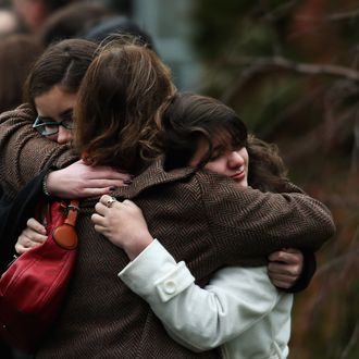 Three women embrace as they arrive for the funeral services of six year-old Noah Pozner, who was killed in the shooting massacre in Newtown, CT, at Abraham L. Green and Son Funeral Home on December 17, 2012 in Fairfield, Connecticut. Today is the first day of funerals for some of the twenty children and seven adults who were killed by 20-year-old Adam Lanza on December 14, 2012.