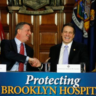 New York City Mayor Bill de Blasio, left, and New York Gov. Andrew Cuomo shake hands during a news conference in the Red Room at the Capitol on Monday, Jan. 27, 2014, in Albany, N.Y. De Blasio is urging state lawmakers to support his proposed tax hike on wealthy city residents to pay for universal prekindergarten. (AP Photo/Mike Groll)