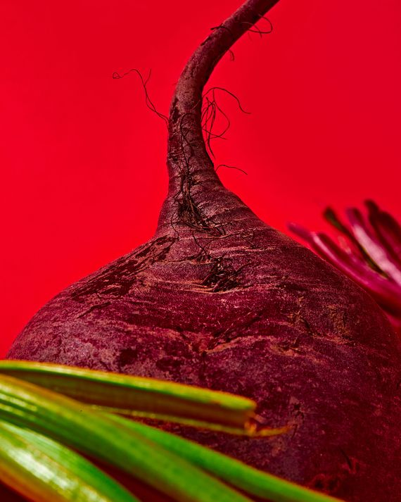 An ultra close-up of a raw beet against a red background
