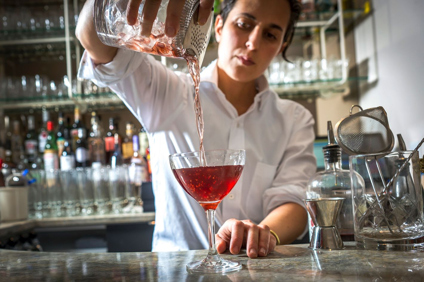 Bartender Soraya Odishoo making the Oakland cocktail, which includes smoked red wine, bitters, and golden rum.