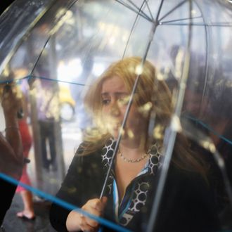 A woman walks through the rain under an umbrella on 5th Avenue in Midtown Manhattan on July 15, 2014 in New York City.