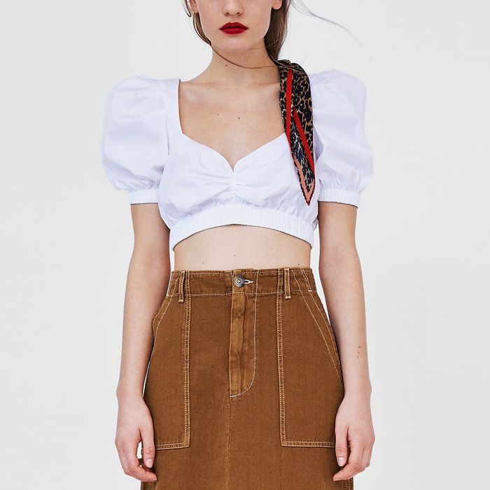 A trendy puffy, white cropped blouse from Zara, in a post by the Strategist on German dirndl blouses.
