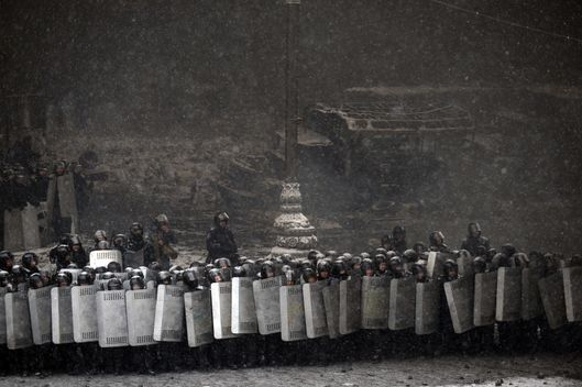 Riot police stand with raised shields during clashes with protestors in the centre of Kiev on January 22, 2014. Ukrainian police today stormed protesters' barricades in Kiev as violent clashes erupted and activists said that one person had been shot dead by the security forces. Total of two activists shot dead during clashing. The move by police increased tensions to a new peak after two months of protests over President Viktor Yanukovych's failure to sign a deal for closer ties with the EU. AFP PHOTO/ VASILY MAXIMOV        (Photo credit should read VASILY MAXIMOV/AFP/Getty Images)