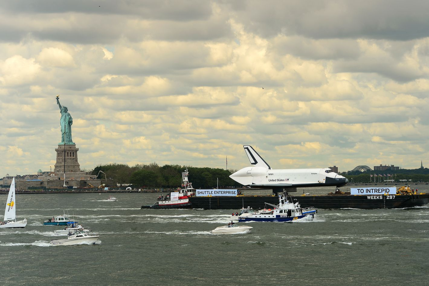 The space shuttle Enterprise is towed atop a barge going by the Statue of Liberty as it is viewed from the Staten Island ferry in New York, June 6, 2012. Enterprise was moved by barge to the Intrepid Sea, Air and Space Museum in New York where it will be permanently displayed.