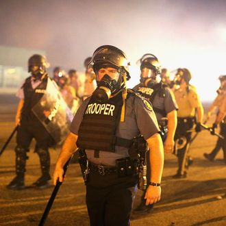 FERGUSON, MO - AUGUST 17: Police advance through a cloud of tear gas toward demonstrators protesting the killing of teenager Michael Brown on August 17, 2014 in Ferguson, Missouri. Police shot smoke and tear gas into the crowd of several hundred as they advanced near the police command center which has been set up in a shopping mall parking lot. Brown was shot and killed by a Ferguson police officer on August 9. Despite the Brown family's continued call for peaceful demonstrations, violent protests have erupted nearly every night in Ferguson since his death. (Photo by Scott Olson/Getty Images)