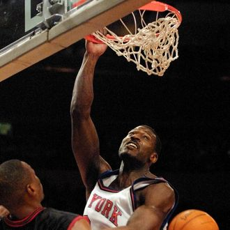 New York Knicks forward Larry Johnson (R) dunks the ball in front of Philadelphia 76ers forward Theo Ratliffe (L) during the third quarter 01 February, 2001 at Madison Square Garden in New York City. The 76ers beat the Knicks 87-80.