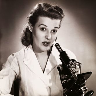 Portrait of a female scientist using a microscope