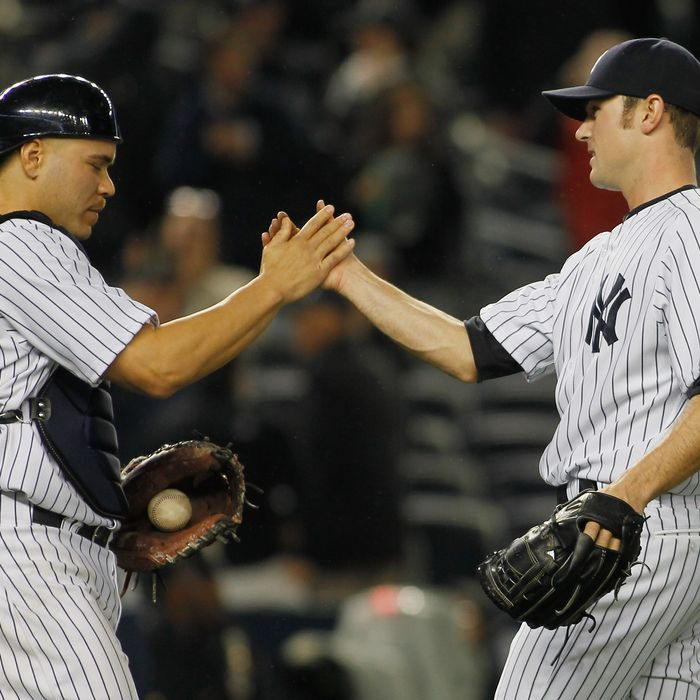 David Robertson #30 of the New York Yankees is congradulated by teammate Russell Martin #55 of the New York Yankees after defeating the Tampa Bay Rays at Yankee Stadium on May 8, 2012 in the Bronx borough of New York City. Yankees defeated the Rays 5-3.
