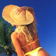 Young Woman at Beach in Bikini and Straw Hat