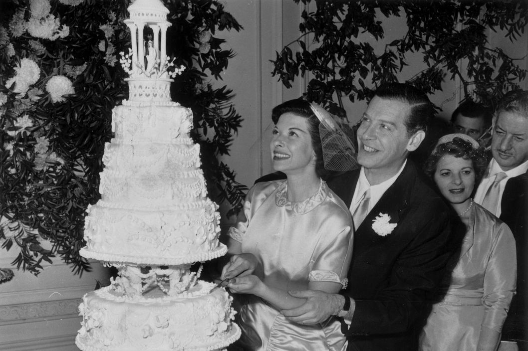 1953:  American comedian Milton Berle (1908 - 2002) stands behind his new bride, Ruth Cosgrove, as she slices into their wedding cake during their reception.