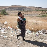 10 Aug 2014, Sinjar, Iraq --- FISHKHABOUR, IRAQ: A Yezidi woman carries her child to shelter after crossing from Syria back into Iraq. Tens of thousands of Yezidi--an minority ethno-religious group in Iraq--have made there way to safety after being stranded on Mt. Sinjar. They escaped to the mountain after coming under attack by ISIL (The Islamic State of Iraq and the Levant). After days of being stranded, they were able to safely descend the mountain into Syria and then cross back into Iraq further north. --- Image by ? Sebastian Meyer/Sebastian Meyer/Corbis