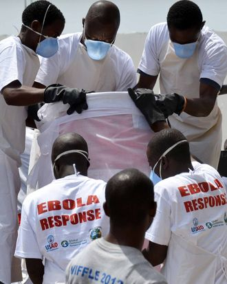 Workers at the crematorium wearing protective equipment take a barrel containing victims of Ebola's remains in a car on March 7, 2015 in Monrovia to be taken to the safe burial site.