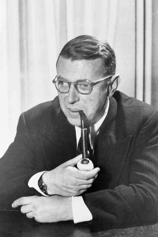 01 Mar 1949 --- Waist-up portrait of French philosopher and author Jean-Paul Sartre.  Sartre is seated and is smoking a pipe.
