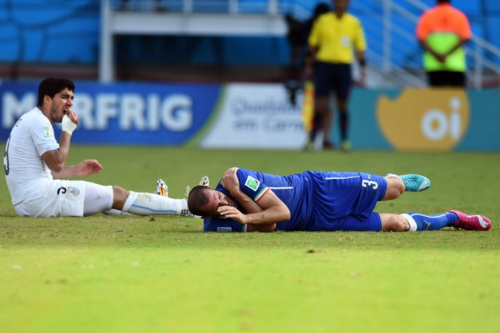 Uruguay's forward Luis Suarez (L) reacts past Italy's defender Giorgio Chiellini during a Group D football match between Italy and Uruguay at the Dunas Arena in Natal during the 2014 FIFA World Cup on June 24, 2014.   AFP PHOTO/ JAVIER SORIANO