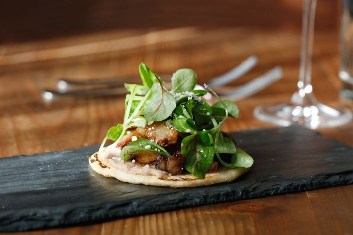 Arepa with heirloom-bean purée, maple-syrup-glazed pork belly, sorrel, and cotija cheese.
