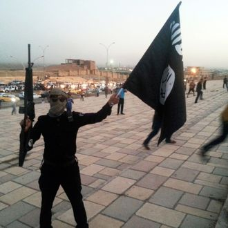 A fighter of the Islamic State of Iraq and the Levant (ISIL) holds an ISIL flag and a weapon on a street in the city of Mosul in this June 23, 2014 file photo.