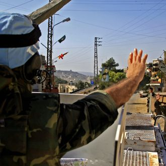 A Spanish UN soldier waves to a Lebanese soldier as he patrols the village of Adaisseh in south Lebanon, 12 November 2006. In the land of Hezbollah, in south Lebanon, the blue helmet Spanish soldiers intend to show they are there to help and dispel misunderstandings.