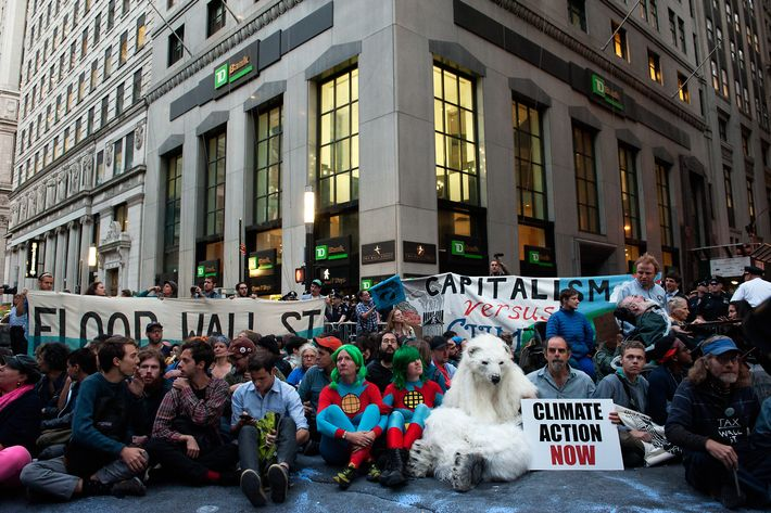 NEW YORK, NY - SEPTEMBER 22: Demonstrators sit in the middle of Broadway during the Flood Wall Street protest on September 22, 2014 in New York City. The Flood Wall Street protest came on the heels of the climate change march on September 21 that attracted over 300,000 protestors. (Photo by Bryan Thomas/Getty Images)