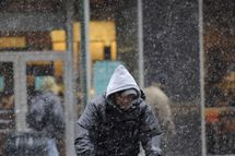 A man on a bicycle makes a food delivery as snow falls over Manhattan, in New York, February 3, 2009. New York City was expecting some four inches (10.16cm) of snow across the five boroughs, according to the National Weather Service.