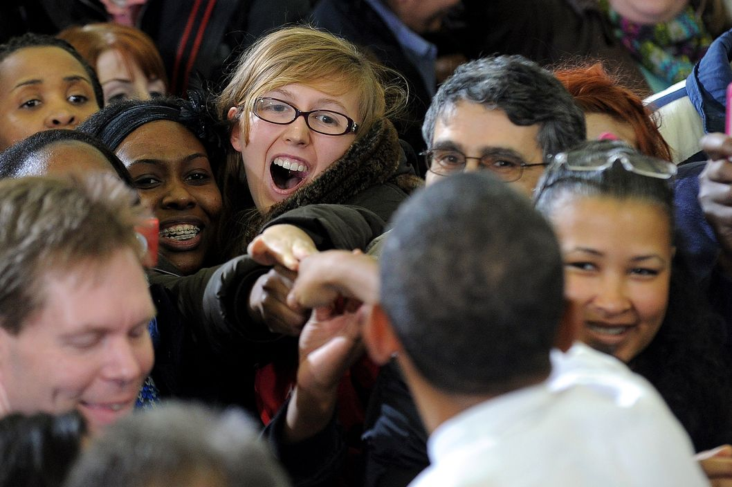 US President Barack Obama greets students and other attendees after speaking at the University of Michigan