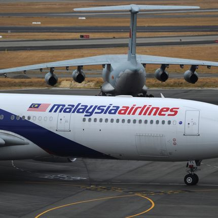 A Malaysia Airlines plane (below) prepares to go onto the runway and pass by a stationary Chinese Ilyushin 76 aircraft (top) at Perth International Airport on March 25, 2014. Wild weather halted the search on March 25 for wreckage from the Malaysia Airlines jet that crashed into the Indian Ocean, frustrating attempts to determine why it veered off course and bring closure to grieving relatives. AFP PHOTO / POOL / Greg WOOD