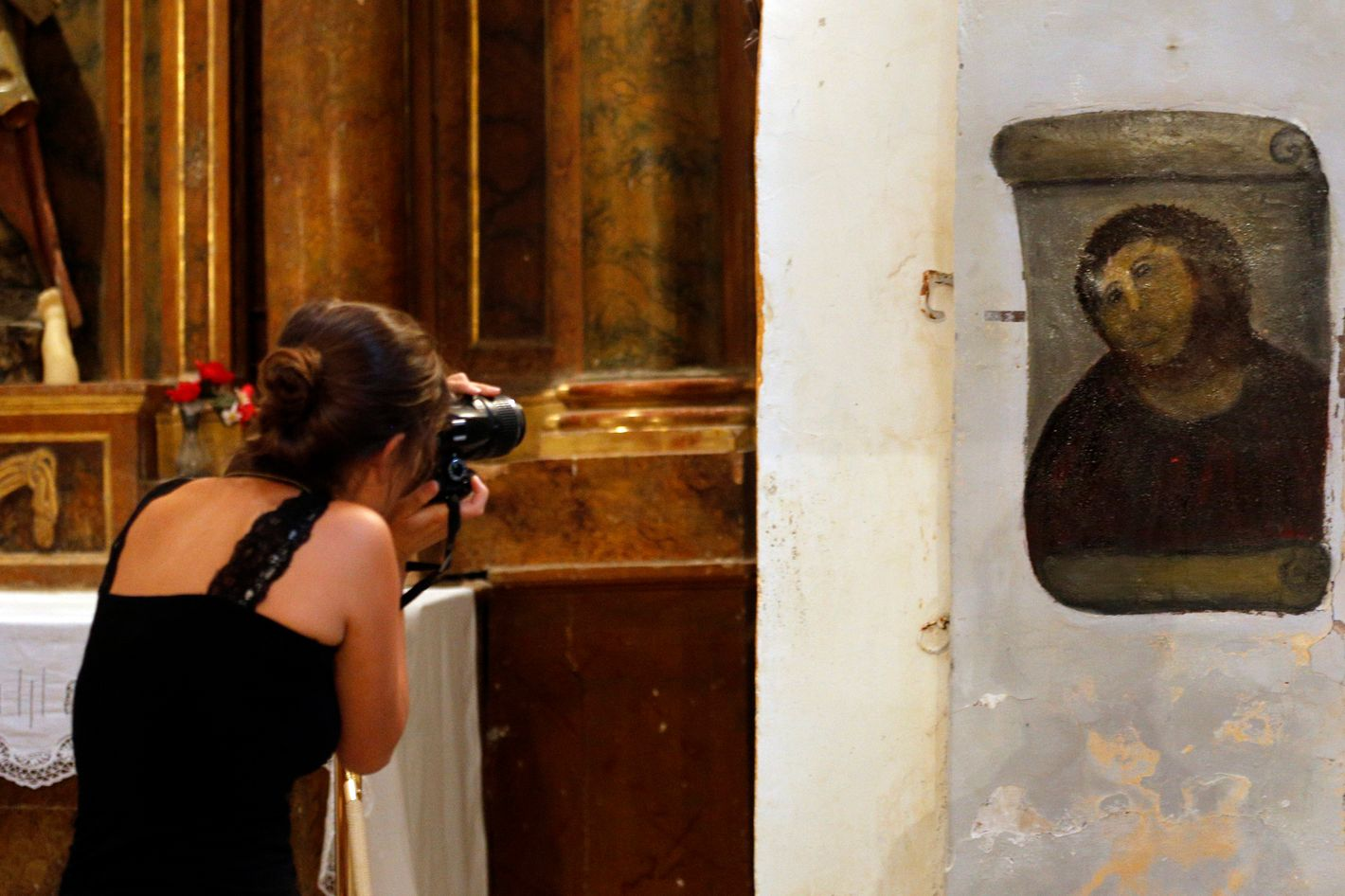 "A woman takes pictures of the deteriorated version of ""Ecce Homo"" by 19th-century painter Elias Garcia Martinez, at the Borja Church in Zaragoza on August 28, 2012. An elderly woman's catastrophic attempt to ""restore"" a century-old oil painting of Christ in a Spanish church has provoked popular uproar, and amusement. Titled ""Ecce Homo"" (Behold the Man), the original was no masterpiece, painted in two hours in 1910 by a certain Elias Garcia Martinez directly on a column in the church at Borja, northeastern Spain. The well-intentioned but ham-fisted amateur artist, in her 80s, took it upon herself to fill in the patches and paint over the original work, which depicted Christ crowned with thorns, his sorrowful gaze lifted to heaven."