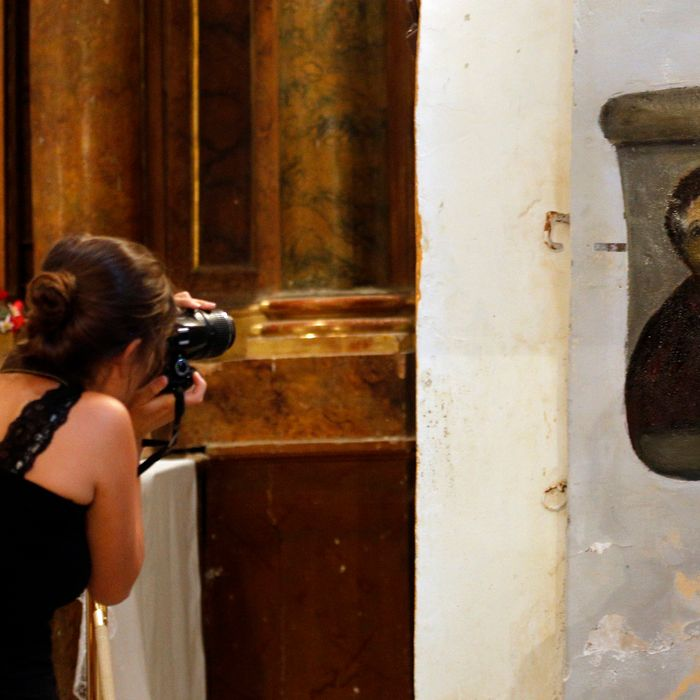 A woman takes pictures of the deteriorated version of