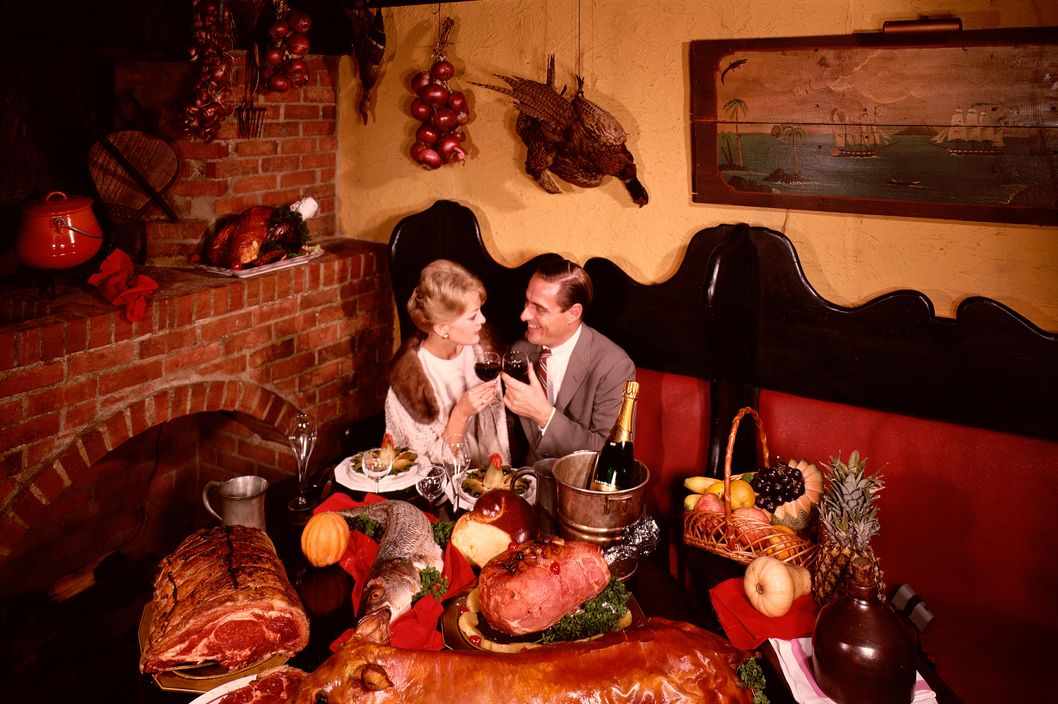 October 1965 --- A couple dines at a table filled with an extraordinary variety of meats and special dishes at the Jamaica Arms Restaurant in New York City. --- Image by ? Charles E. Rotkin/CORBIS