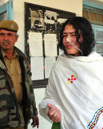TO GO WITH India-unrest-Manipur-politics,FEATURE by Abhaya Srivastava A policewoman escorts civil rights activist, Irom Sharmila Chanu (R) also known as the